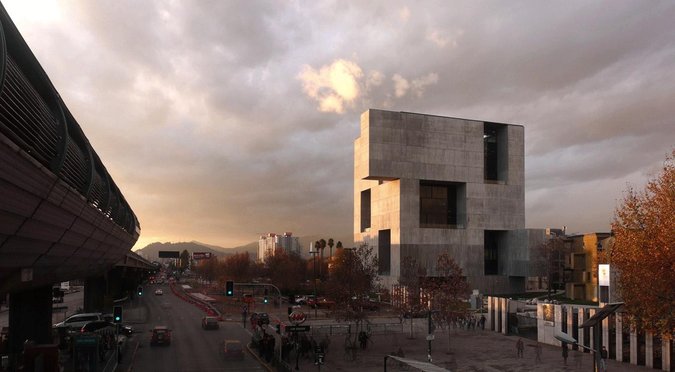 Monolithe de béton vu de l'extérieur au crépuscule, lumière orangée